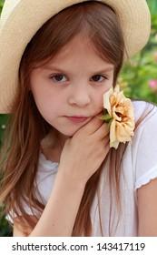 Cute little girl wearing a hat in the summer garden