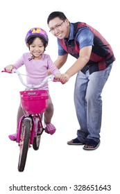 Cute little girl wearing helmet and try to ride a bicycle with her dad, isolated on white background