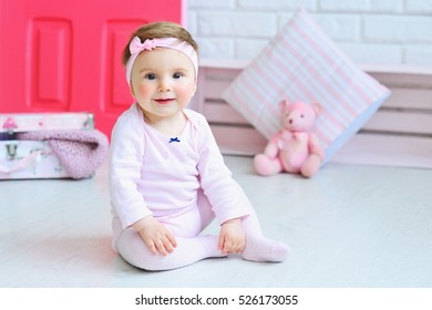 Cute little girl wearing pink clothes and trendy headband with a bow