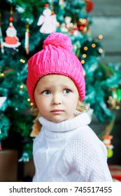cute little girl wearing a pink hat at home with Christmas tree