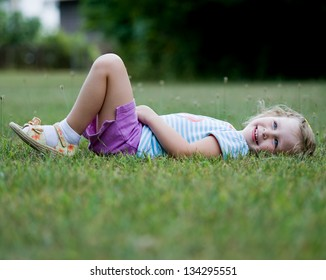 Cute little girl wearing purple shorts and blue striped shoes with flowered sandals laying in grass and smiling