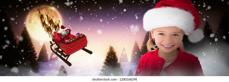 Cute little girl wearing santa hat against full moon over snowy landscape and house