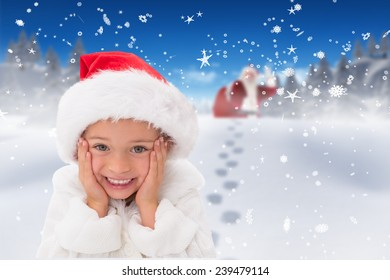 Cute little girl wearing santa hat against bright blue sky over clouds