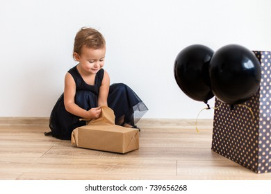 Cute little girl wearing stylish black dress with black balloons, open gift for bithday. Black friday concept. Stylish birthday look