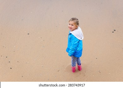 A cute little girl wearing warm clothes- a jacket and gumboots standing in the sand at the beach and looking up with a sandy beach at the background.