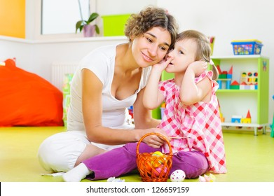 Cute little girl whispering to her mother during Easter eggs painting