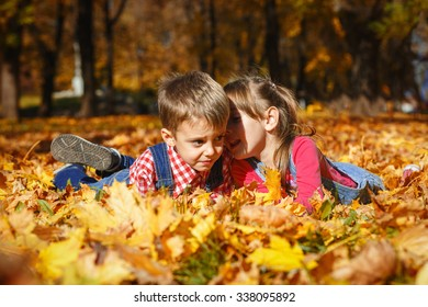 A cute little girl whispering to her brother lying on autumn leaves