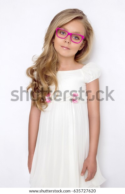 Cute little girl in a white communion dress, standing on a pink background