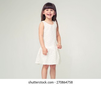Cute little girl in white dress smiling on camera with long hair