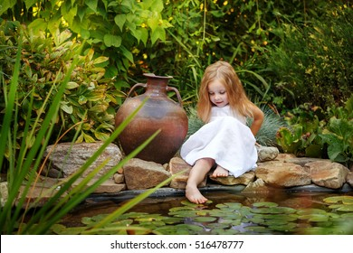 a7eecfc9be7 Cute little girl in a white dress wets feet in the pond with lilies. Big