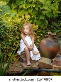 d8cb27d7e50 Cute little girl in white dress sitting by the pond with lilies. Old clay  jug