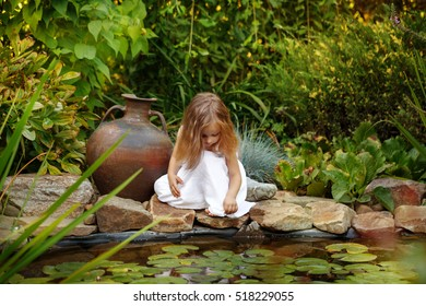 f643ed0a6f5 Cute little girl in a white dress looks into the pond with lilies. Big old