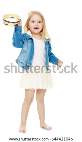 e7710b3e3d6 Cute little girl in white dress and denim jacket strikes a tambourine. Isolated on white