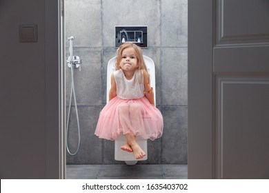 Cute little girl in white pink dress sitting on toilet on background of walls with gray tiles, view from open door.