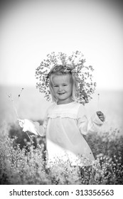 Cute little girl in a white shirt and a wreath on his head is in the yellow field under blue sky