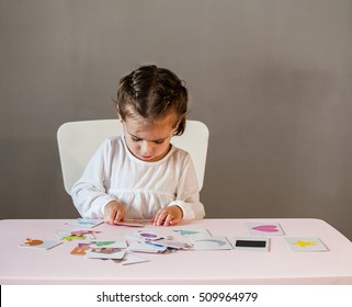 Cute little girl in white shirt playing puzzle. Process of education, cognition