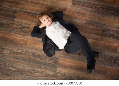 Cute little girl in a white shirt and trousers lies on a floor. Fashion concept