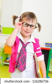 Cute little girl win eyeglasses and necktie with notebook folder