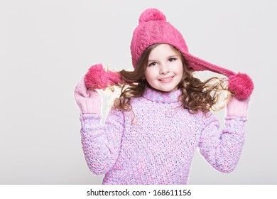 Cute little girl in winter woolen accessories. Adorable baby girl portrait in studio. Happy Little girl in winter hat and gloves. Space and white background.