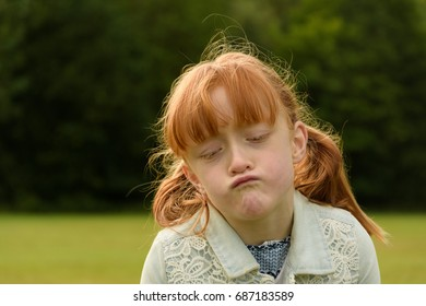 cute little girl wit ginger hair outdoors pulling a funny face