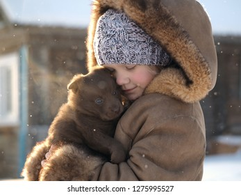 Cute little girl with a wonderful puppy in her arms. Snow, winter. Portrait of a child with a dog