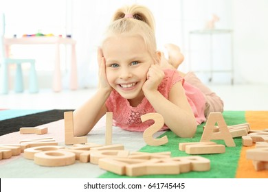 Cute little girl and word LISA composed of wooden letters on floor at home