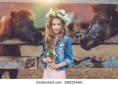 Cute little girl with wreath of flowers playing  near horses ponies in the stables over sunset