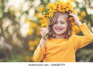 Cute little girl with wreath of yellow flowers on head over sunset playing in  park