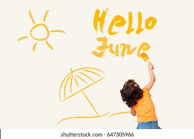 Cute little girl writing Hello June - using painting brush on wall background