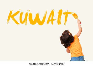 Cute little girl writing KUWAIT with painting brush on wall background
