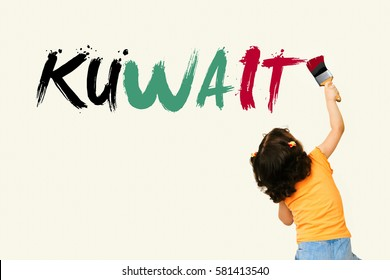 Cute little girl writing KUWAIT with flag  colors using painting brush on wall background