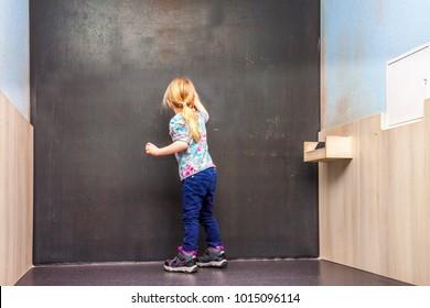 Cute little girl writing on empty chalkboard in a classroom