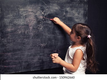 cute little girl writing something with a pink chalk on blackboard