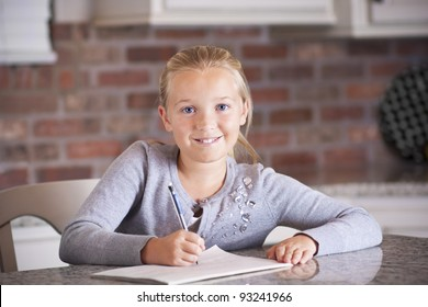 Cute little girl writing and studying in her notebook