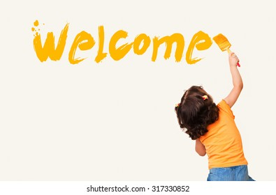 """Cute little girl writing """"Welcome"""" with painting brush on wall background"""
