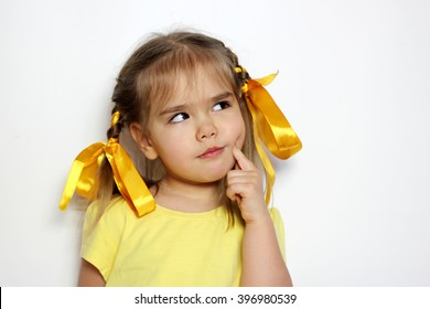 Cute little girl with yellow bows and yellow T-shirt thinking over white background, sign and gesture concept
