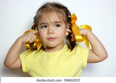 Cute little girl with yellow bows and yellow T-shirt covering her ears with her fingers over white background, sign and gesture concept