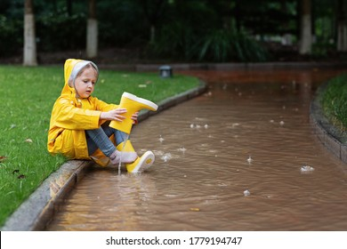 Cute little girl in yellow raincoat and rubber boots walking outdoor during rain. Bad weather, summer tropical storm, autumn fashion concept.
