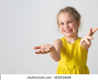 Cute little girl in yellow summer clothing looking at camera with smile lending her hands willingly to help someone. Childhood, expression, assistance. Waist-up shot isolated on white, copy space