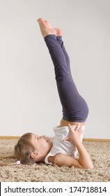 Cute little girl yoga exercising at home