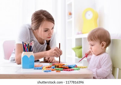 Cute little girl with young nanny at table, indoors