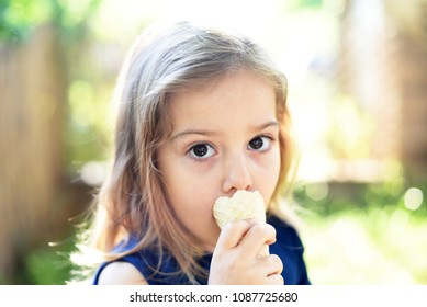 Cute little girleating ice cream at sunset. Little girl eat ice cream in close up face feeling delicious. Kid with dirty face eating ice cream