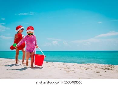 cute little girls celebrating christmas on tropical beach