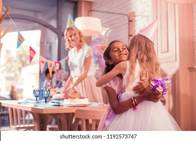 Cute little girls. Cheerful kind girl hugging her best friend while greeting her at the birthday party