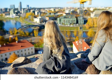 Cute little girls enjoying a view of Vilnius city from the Gediminas hill on sunny autumn day. Exploring tourist attractions with kids.
