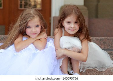 Cute little girls with long hair in long white dresses sitting on the steps
