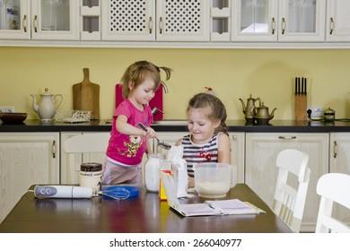 Cute little girls making pie in the kitchen.