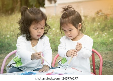 Cute little girls are painting with watercolor together in soft style