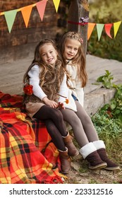 Cute little girls posing over wooden house background. Autumn concept.