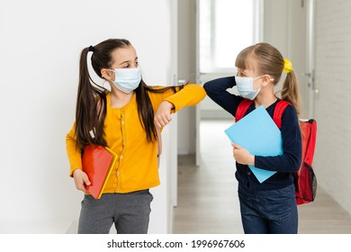 Cute little girls of primary hug each other with the mask on. School girls carry notebooks in hand and greet each other before entering school.
